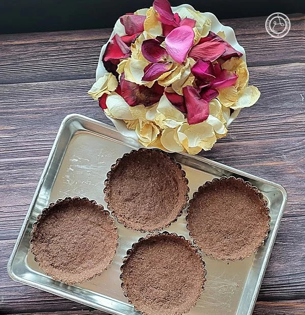 Gluten-Free Chocolate Tart Shells pictured is 4 tarts and rose petals.