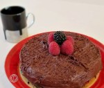 Fosted Gluten-Free Chocolate Fudge Cake with berries and a black espresso coffee cup