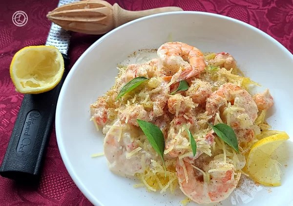 Gluten-Free Creamy Seafood Alfredo on a plate with a zester, juicer, and half a lemon to the side.