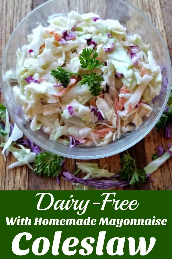 Coleslaw on a table with cabbage and parsley surrounding the bowl and parsley to deorate the slaw.