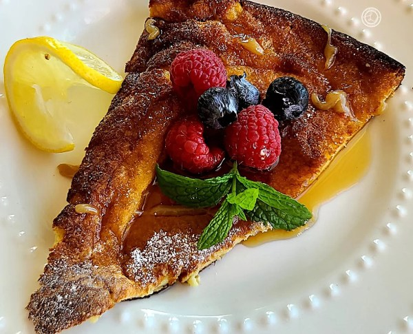 A slice of Dutch Pancake with raspberry, blueberries, lemon slice, maple syrup, and sprig of mint.