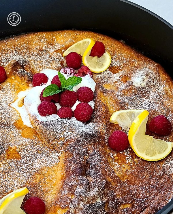 Dutch pancake with raspberries, whipped cream, and slices of lemon.