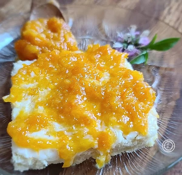 A gluten-free piece of toast with Orange Marmalade, a spoonful of marmalade and basil flowers.