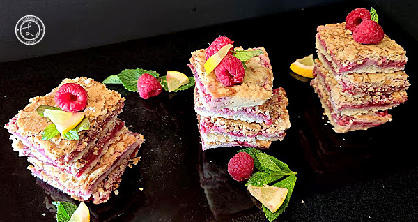 A beautiful array of these tasty treats on a black background with lemon wedge, mint, and raspberries.