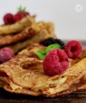A close-up of two stacks of folded crepes with raspberries, blackberries, and a sprig of mint