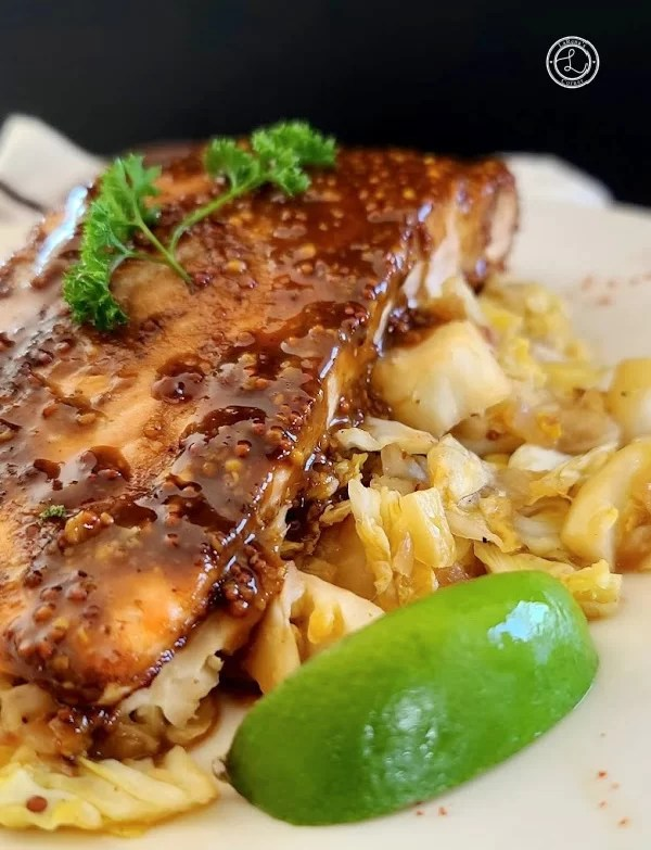 Mustard Glazed Salmon on a bed of Mustard Caraway Fried Cabbage on a white plate