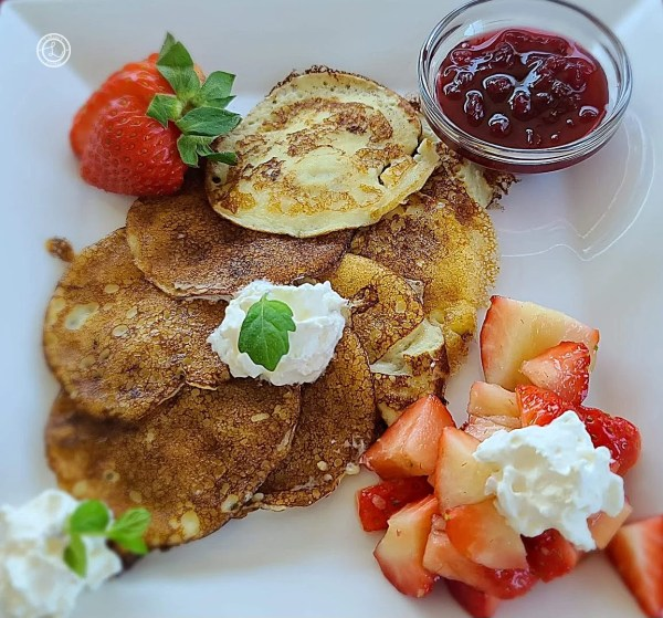 A plate of Swedish Pancakes, with a strawberry, lingonberry jam, whipped cream, and sprigs of mint