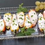 Lobster Dip inside Baby Bell Peppers on a clear platter with mint leaves and grapes