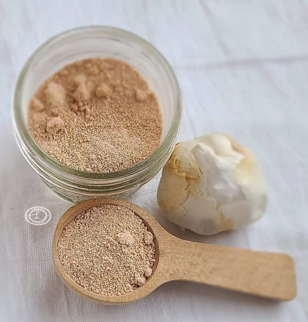 Sweet Smokey BBQ Rub in a jar and on a spoon with a bulb of garlic to decorate. All on white background