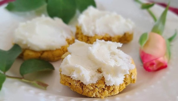A close up of 3 Cream Cheese Cinnamon Frosted Pumpkin Cookies