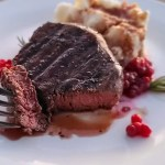 Elk Steak with Red Wine Balsamic Reduction, cauliflower mash, and lingonberries, with a sprig of rosemary