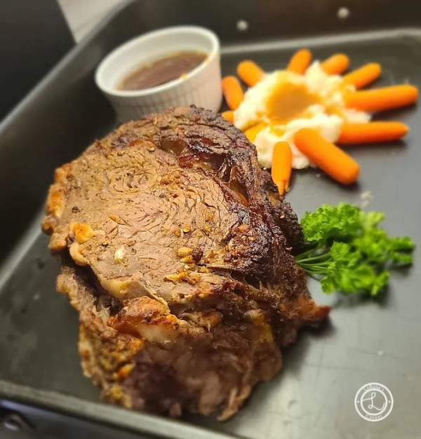 Cooked Prime Rib with mashed potatoes, gravy, carrots, and au jus.