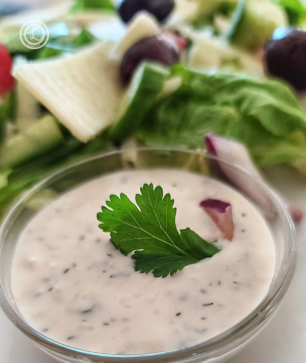 A close up of the Dairy-Free Ranch Horseradish Dressing with a salad in the background