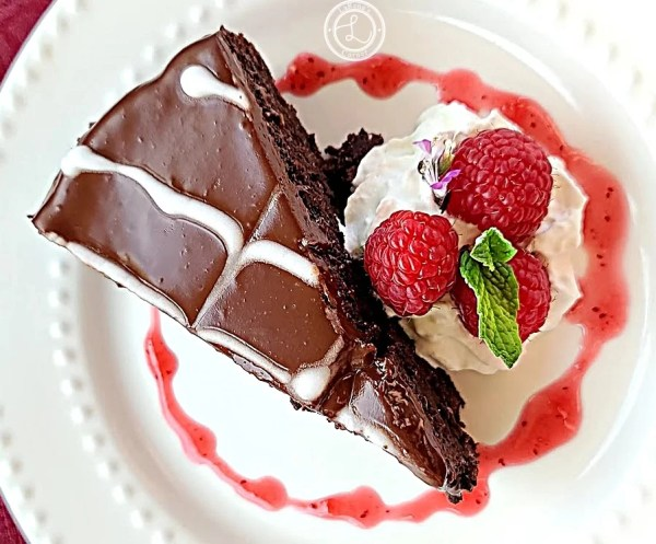A slice of cake with raspberries and whipped cream.