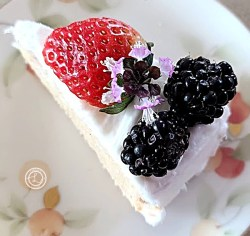 A slice of cake with frosting and fruit