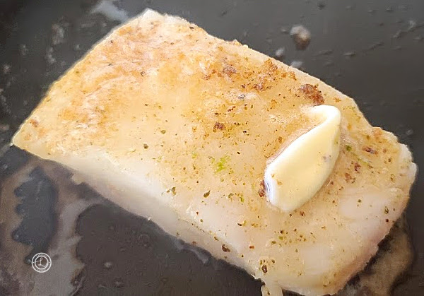 Adding butter to the fish and hot pan