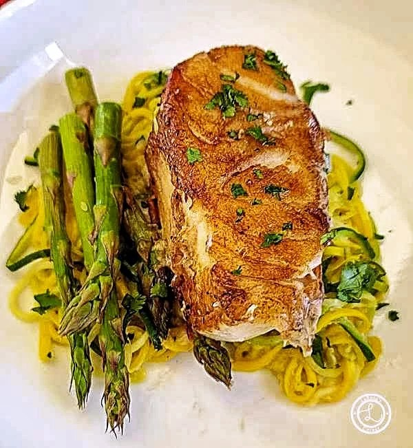 Jalapeno Chilean Sea Bass on a bed of zoodles with asparagus spears.