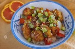 Gluten-Free Orange Chicken in a bowl topped with green onions and roasted sesame seeds.