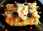A piece of Grilled Maple Sausage Casserole on a plate with sour cream and more diced baby bell pepper.