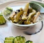 A bowl of horseradish pickles and some cut up cucumbers with mustard seeds