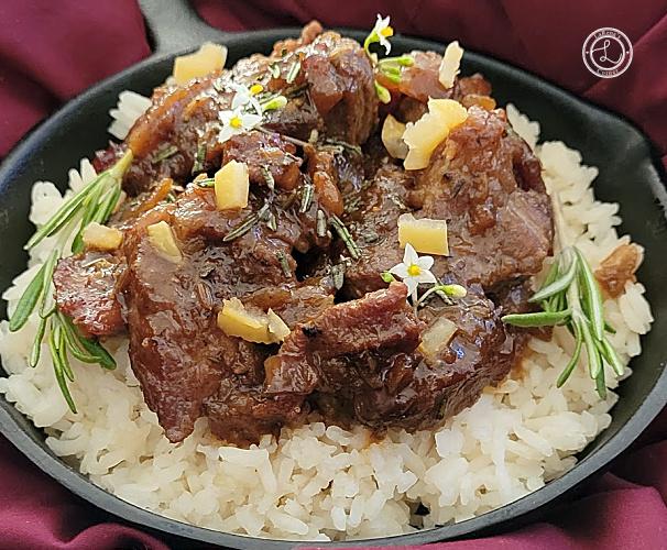 Greek Braised Rosemary Pork with Rosemary Sprigs, basil flowers, and preserved chopped lemons.