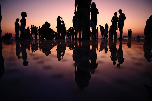 A crowd at a party with water showing their reflection in silhouette
