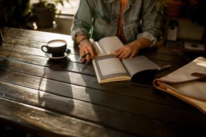 Person sitting at table with book and notebook open
