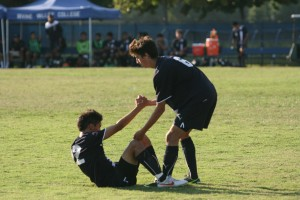 Alex Cannis (6) of IVC helps up fellow teammate Adriel Trejo (22) after he was injured in the later minutes of the game.  (Evan Da Silva )