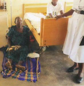 Ill Ugandan woman sits on floor of Atutur Hospital due to lack of hospital beds. (Frederick Malinga)