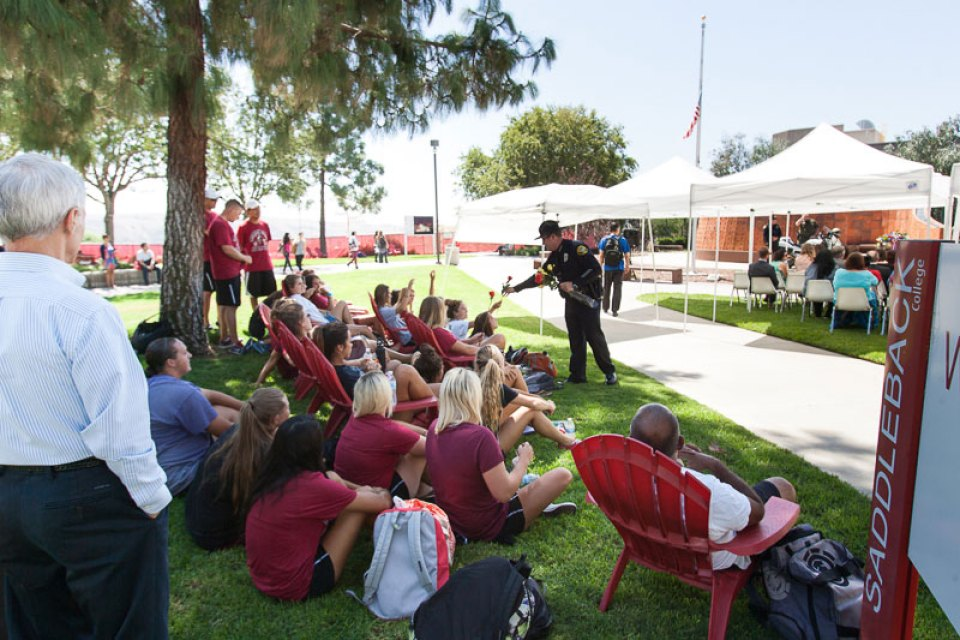 Saddleback College Police Chief Christopher Wilkinson hands out roses to Saddleback College students. Before the start of the 9/11 ceremony. Students later placed the roses at the foot of the memorial wreath. (Zachary Epstein/Lariat)