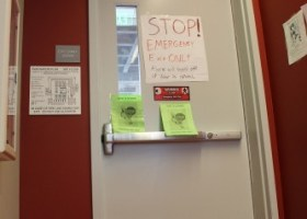 """""""Emergency"""" door being plastered with amateurish """"Stop! Do not use door!"""" signs. (Photographer/Hannah Tavares)."""