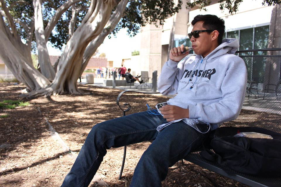 Jerrin Hilliado, a sports medicine major, 18, smokes from an electronic vaporizer. These are most commonly used as a substitute for cigarettes, although exhalation releases a vapor versus smoke. However, the ban will also include any type of e-cig, vaporizer or chewing tobacco. (Niko LaBarbera/Lariat)