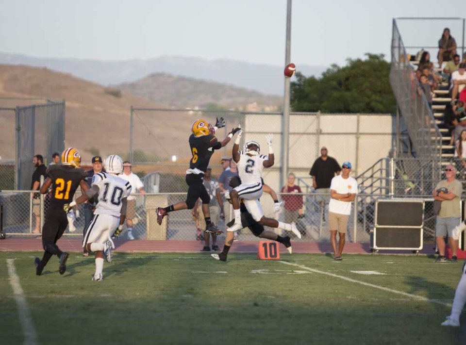 Saddleback's AJ Newman (#6, center) attempts to intercept a pass. The play would result in a touchdown for Cerritos College. (Niko LaBarbera/Lariat)