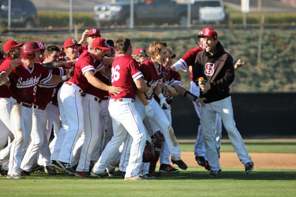 Teammates celebrate and mob Luke Jarvis (blond hair, dirty pant leg) after he hit a game winning single in the second game against Cuesta College. (Nick Nenad)