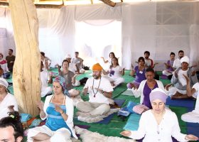 This is common for what a Kundalini Yoga morning session looks like. Prayer and meditation to a higher consciousness is what they are practicing. (Flickr/JAIME RAMOS. Used with a CC BY 2.0 license.)