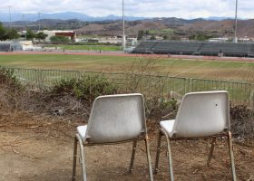 Two chairs sit alone over looking the stadium on the visitors side.