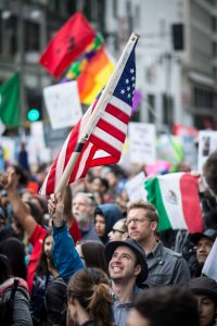 A man looking up with joy at our nations flag. (By Jorge Maldonado)