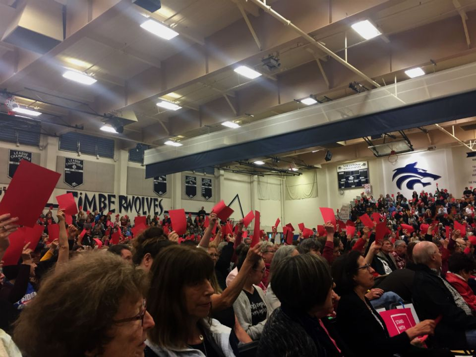 Residents holding up red cards when they disagree on Walters' position. ( Lesley Naranjo / Lariat )