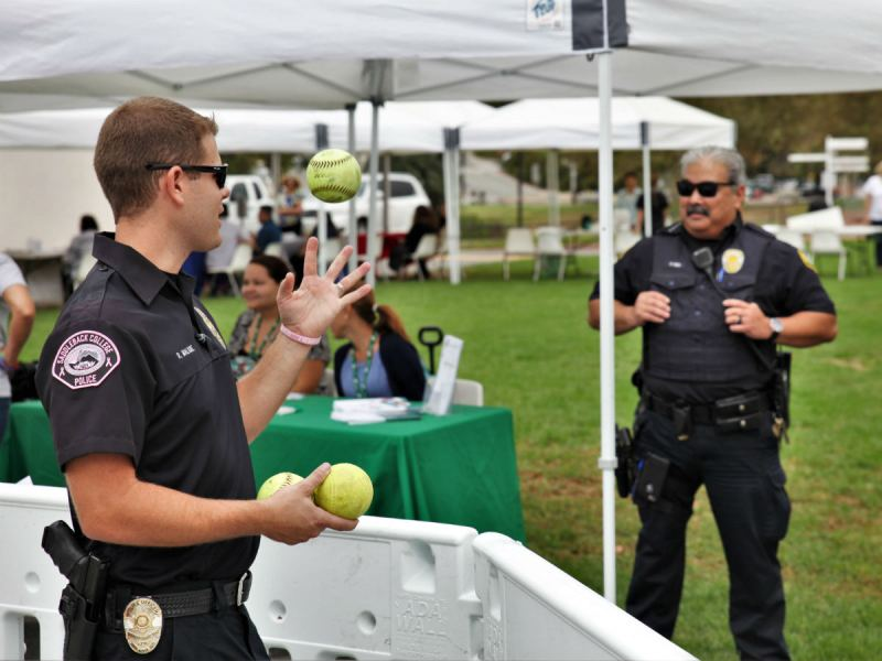 Police Officer Ryan Maligie courts would be fireballers towards the dunk tank as Police Chief Patrick Higa looks over the event (Adam Gilles/Lariat)