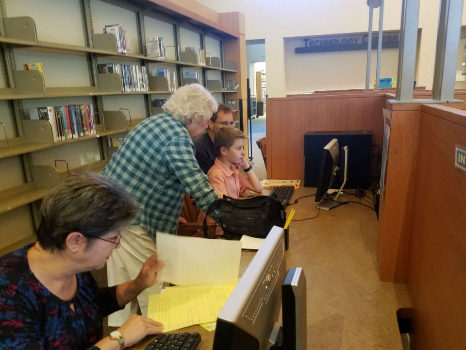 Branch out: Docent helps a family search for ancestry records.