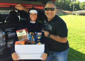 Cheer coach Denise Harris and athletic's executive assistant Jess Perez pose with their food donations on Halloween.