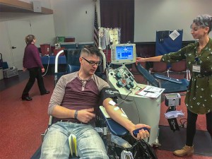 Ryan Lien (left) donates blood while (right) nurse Sara Lopez performs the transfusion. (Lizzie Williams/Lariat)