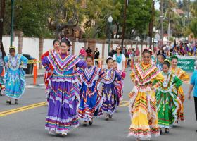 Multiple dancers with colorful attire walking through downtown San Juan Capistrano during Swallow's Day Parade. (Dennis Rex)