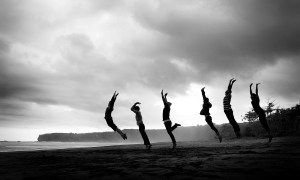 black and white photo of women jumping
