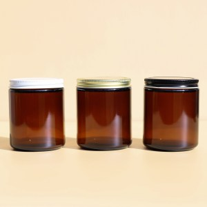 three amber jars lined up, one with a white lid, one with a gold lid and one with a black lid