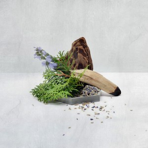 pieces of driftwood with flowers and evergreen sprigs