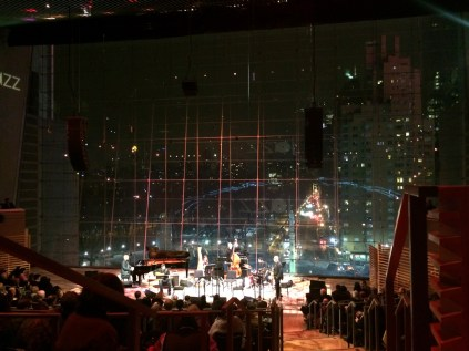 photo of Lincoln Center Jazz stage and Larry Koonse with Billy Childs Chamber Sextet with audience watching, New York city lights visible through enormous background window