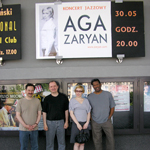 photo of Aga Zaryan Quartet on street beneath sign for Aga Zaryan sign