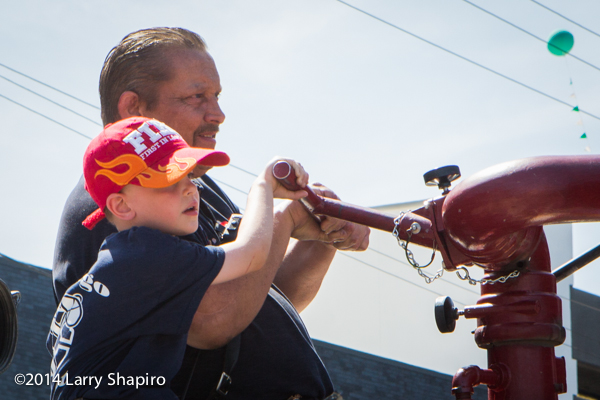 young boy helps father on fire truck
