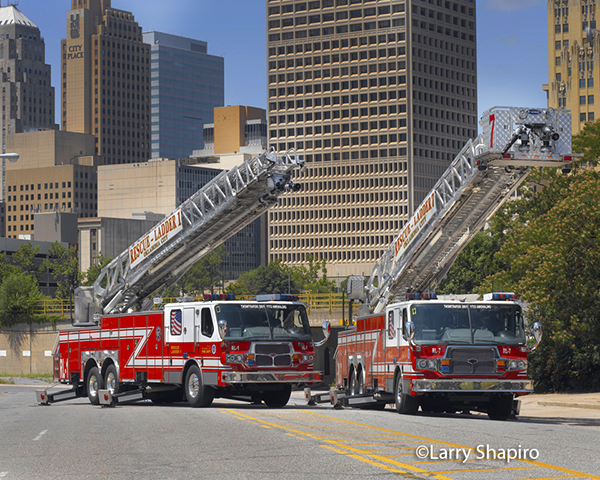 Oklahoma City fire trucks with the city skyline